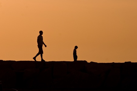 man made: Father and son walking during sunset in Fazana Stock Photo