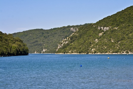 Blue water and green hills of Lim bay photo