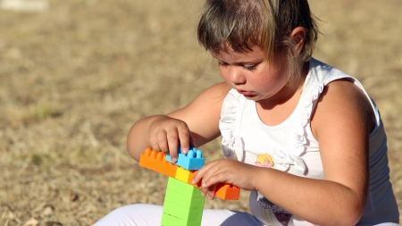 plastic bricks: Little girl building a house with plastic bricks