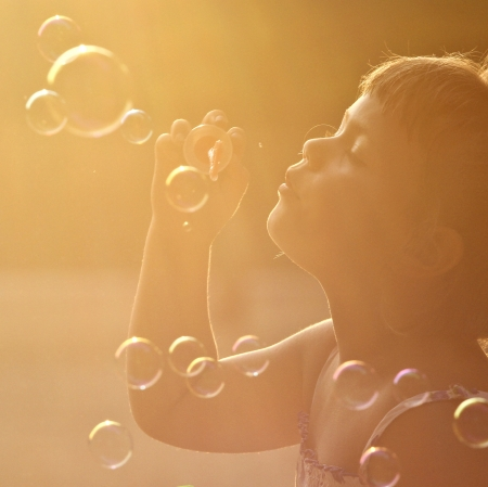 Little girl having fun with soap bubbles       photo