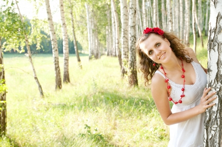 Ukrainian Fashion girl looks out from a tree, a birch grove photo