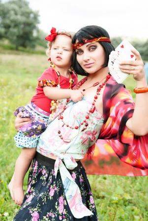 Gypsy woman with her baby wants to tell fortunes by cards, and predict the future