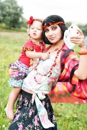 Zigeunerin mit ihrem Baby will Vermögen, indem sie Karten zu erzählen, und die Zukunft vorhersagen