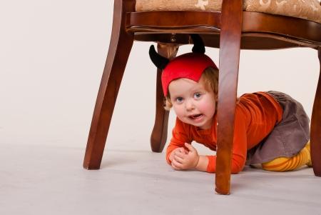 Menina vestida como o diabo sentado debaixo da cadeira e olha