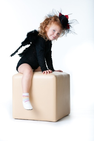 artificial hair: girl angel sitting on a cube, and looks ahead Stock Photo