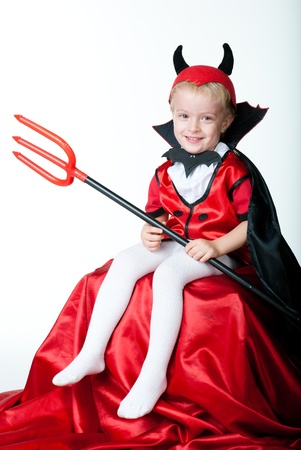 stage costume: devil boy sitting and smiling in his hand he holds a trident Stock Photo