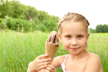 girl holding in their hands and eating ice cream, the girl loves to eat ice cream photo