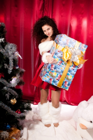 Girl gets a Christmas gift, decorated Christmas tree, red background, beautiful clothes photo
