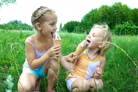 woman with ice cream: Two girls eat ice cream, ice cream One girl shared with another Stock Photo