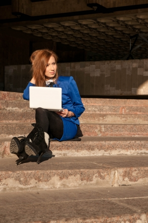 girl works on a computer, sitting on the steps, holding a computer, blue business suit, the sun shines brightly. photo