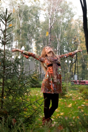 girl enjoys autumn in the city park, autumn, yellow leaves on the trees, Ukraine, raised his hands, throws up yellow leaves, dressed in a gown Stock Photo
