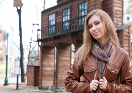 girl on the background of Jewellery in the city park, amusement park, Ukraine, wearing a brown jacket, long hair, long scarf, a nice smile photo
