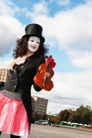 mime playing the violin on the street view Stock Photo