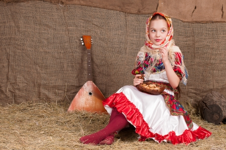 Russian girl in national dress, eating bagels and drinking milk