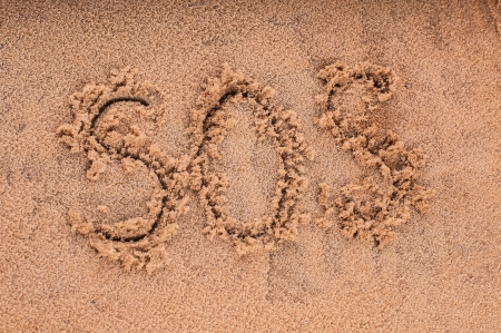 """Drawing of """"SOS"""" on the beach sand at the sea. photo"""