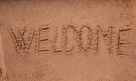 Inscription welcome on a wet sand photo