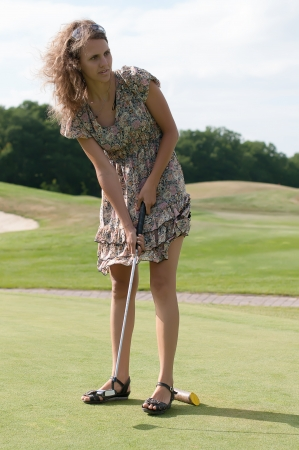 Full length view of 5 year old girl swinging golf club. Stock Photo
