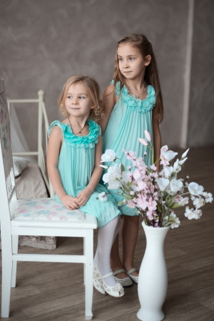 2 little girls in white dresses sitting in looking at you