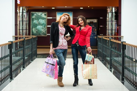 Three beautiful girls with shopping bags in shop
