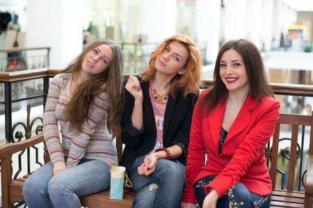 Three girls sitting on a bench in the mall and discuss their purchases Stock Photo