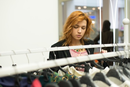 Portrait of a happy attractive teen girl making choices in wardrobe or in shop with clothes photo