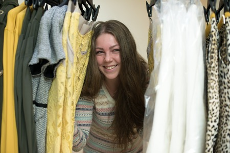 checkroom: Woman choosing clothes from her robe