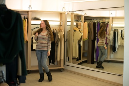 Woman shopping choosing dresses looking in mirror uncertain. Beautiful young multicultural shopper in clothing store. photo