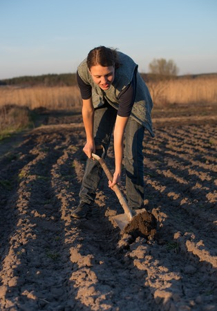 agricultural tools: Female farmer works with manure at field, holding agricultural tools Stock Photo