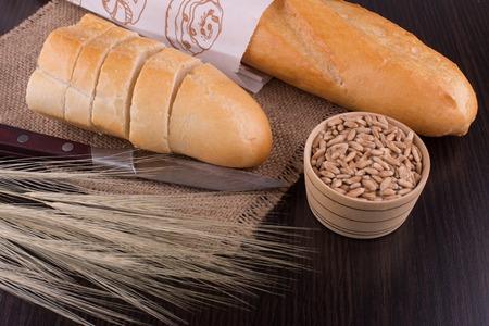 frisches Brot und Weizen auf dem h�lzernen, �hrchen von Weizen