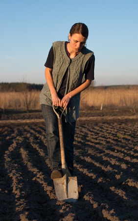 B�uerin arbeitet mit G�lle am Feld, halten landwirtschaftliche Werkzeuge