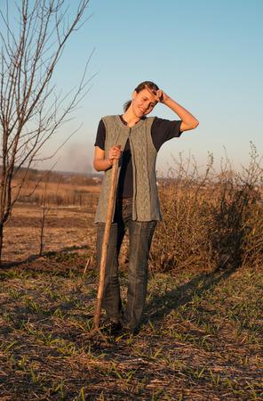hayfork: Female farmer  with spade in plowed field