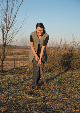 Female farmer  with spade in plowed field photo