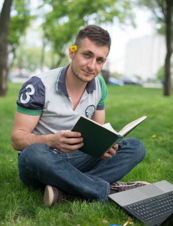 Young man reading Bible in a park photo