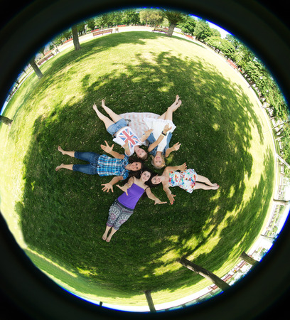 grupa students lie on the grass, photographed by fisheye photo