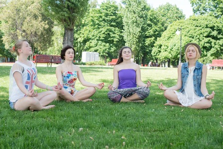 Cute Hispanic women practicing the cobra pose during their yoga class in a gym photo
