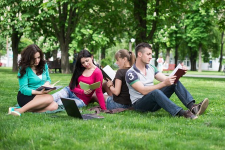 students having lesson outdoor, Students read a book in the park Stock Photo
