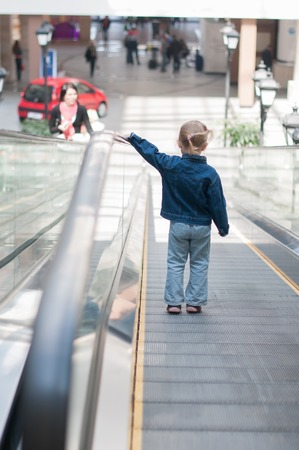 view of a staircase in a shop: Cute little child in shopping center standing on moving staircase, escalator