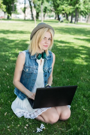 Mixed race college student sitting on the grass working on laptop at campus Stock Photo