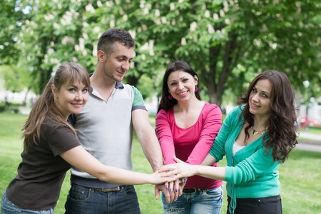 Happy Teenage Group with Hands on Stack, college, relaxation Stock Photo