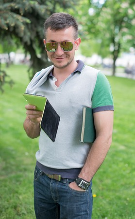 autodidact: serious student with glasses reading book on background of summer park Stock Photo