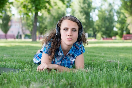 A smiling young girl with laptop outdoors listening music by headphones Stock Photo