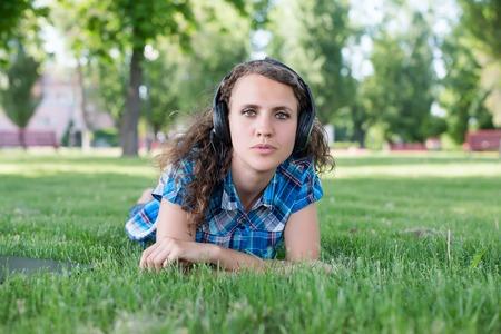 Eine l�chelnde junge M�dchen mit Laptop im Freien Musik h�ren mit Kopfh�rern Lizenzfreie Bilder