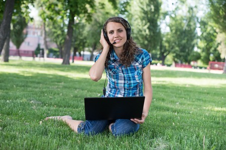 Cute woman in earphones with white laptop in the park photo