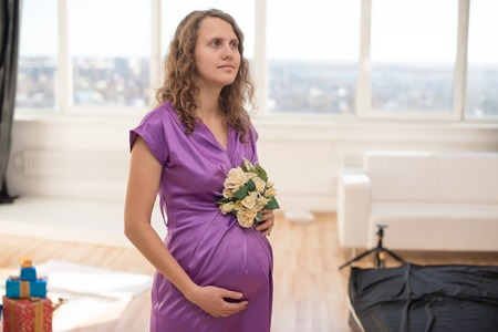 long-haired pretty pregnant woman, against the background of a large window photo