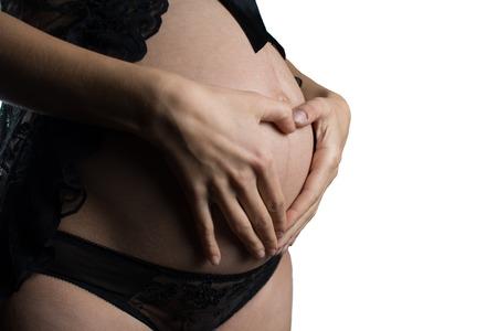 ombligo: Mujer embarazada embarazo concepto coraz�n en el est�mago. Manos que forman el coraz�n en el ombligo femenino. Concepto sano de la salud del est�mago, o el concepto de embarazo temprano con mujeres hermosas manos. Modelo de la mujer. aislado en fondo blanco