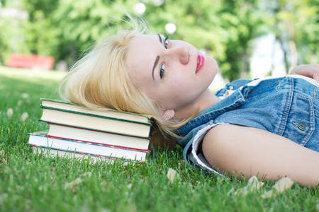 european ethnicity: Beautiful smiling  young woman lying on grass and reading blue book, summer green park. Female student girl outside in park. Happy young university student of mixed European and Caucasian ethnicity.