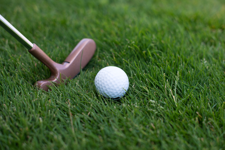 putter: golf ball lying on the grass next to the stick, close of putter and ball Stock Photo