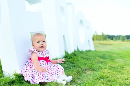 clean environment: Happy lovely kid on the grass floor with the letter.  Child love clean environment