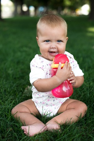 six months: Cute baby girl celebrating 0.5th of July in the park.