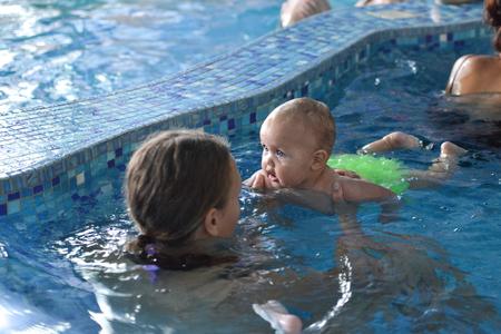 Junge Familie mit Baby Spa� im Pool.